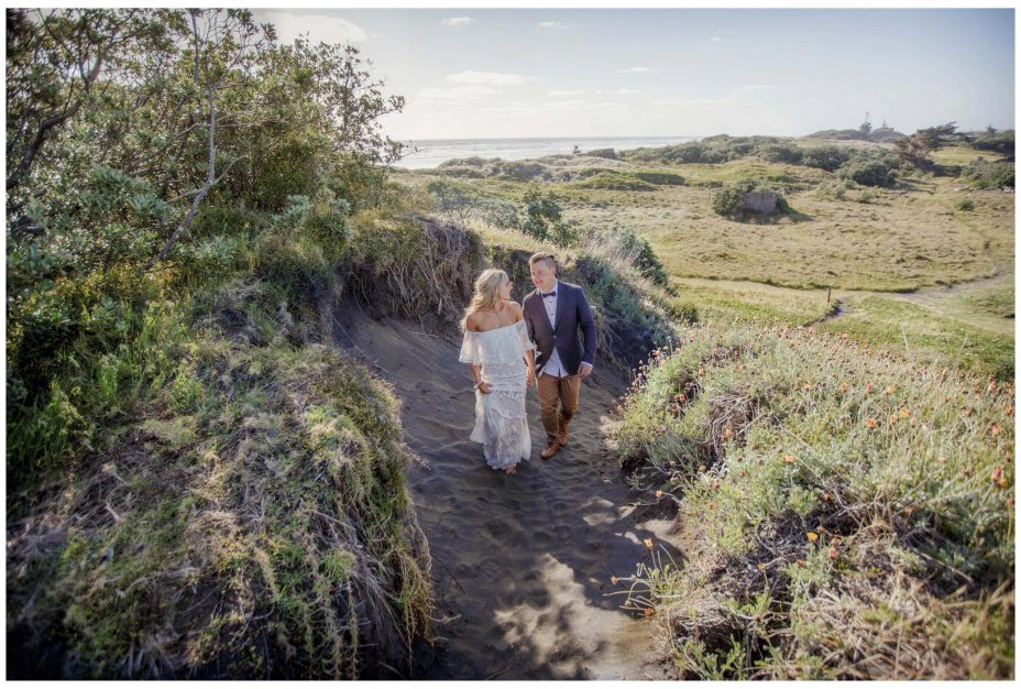 Bride and groom walk together hand in hand , romantic photo, Summer wedding, in sand dunes Murawai Beech, Murawai Beech Wedding photo