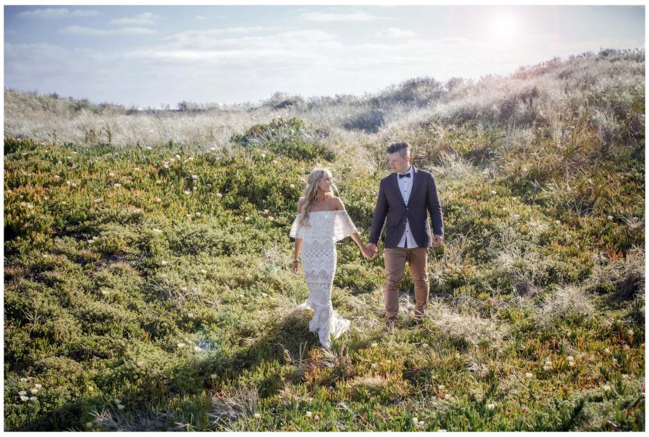BAussie Bride in lace wedding dress and groom hold hands, Murawai Beech romantic sunset weddimg photo,Auckland New Zealand
