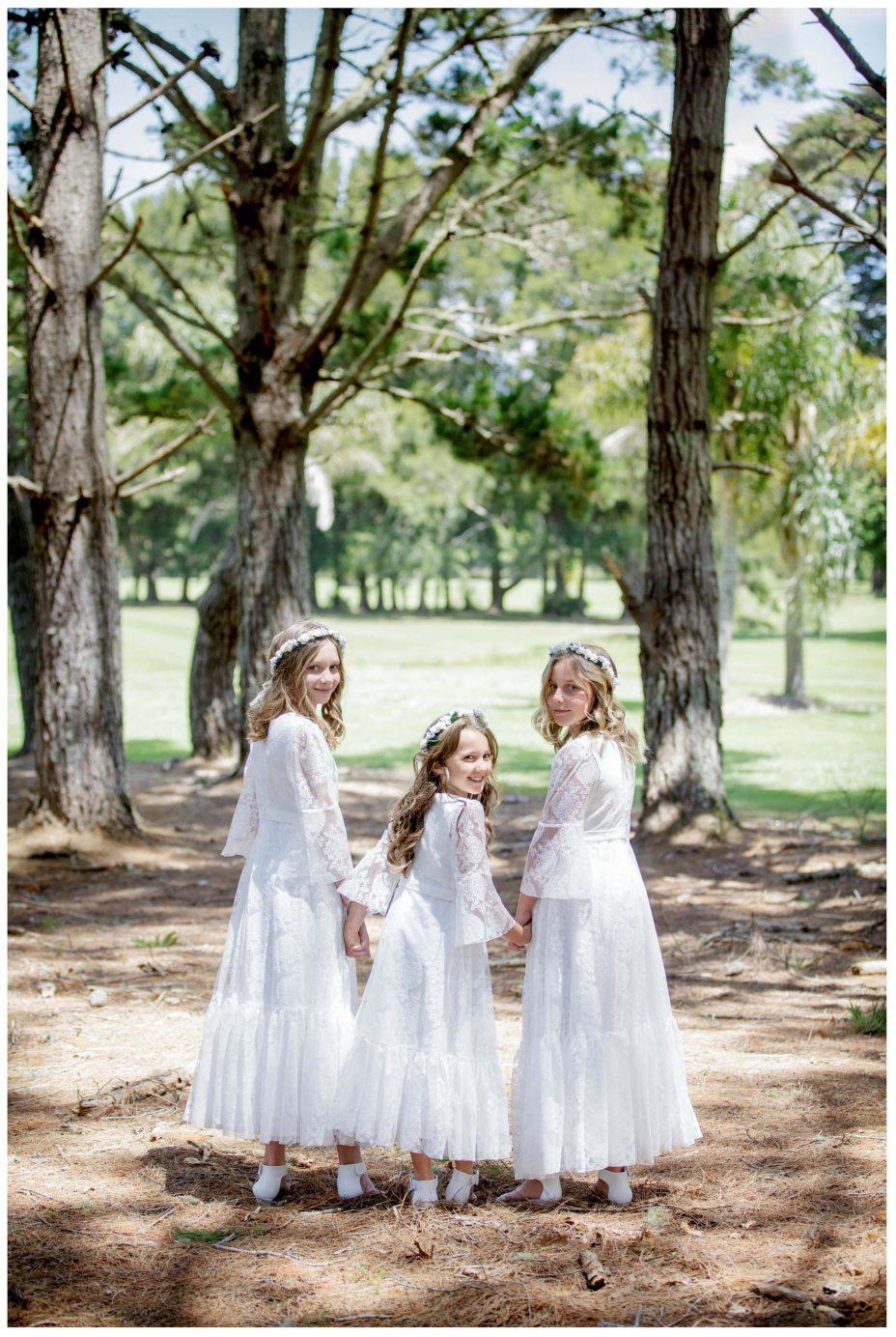 Cute Flower girls in white lace dresses turn to camera smiling, Northridge Estate wedding