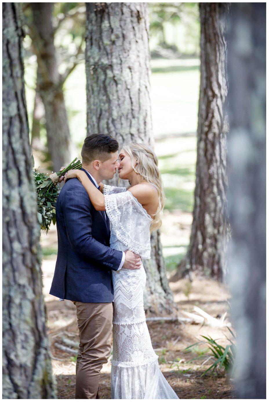 Aussie Bride and groom kiss among the trees, Murawai Beech wedding