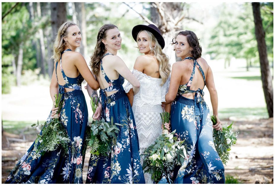 Aussie Bride and bridesmaids in blue floral patterned dress look back to camera, Murawai Beech wedding photo