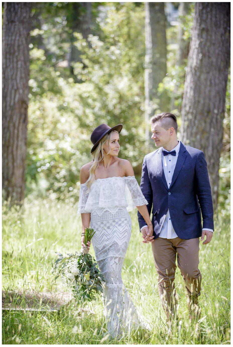 Aussie bride and groom walk together in teh woods, Murawai Beech wedding, Auckland New Zealand