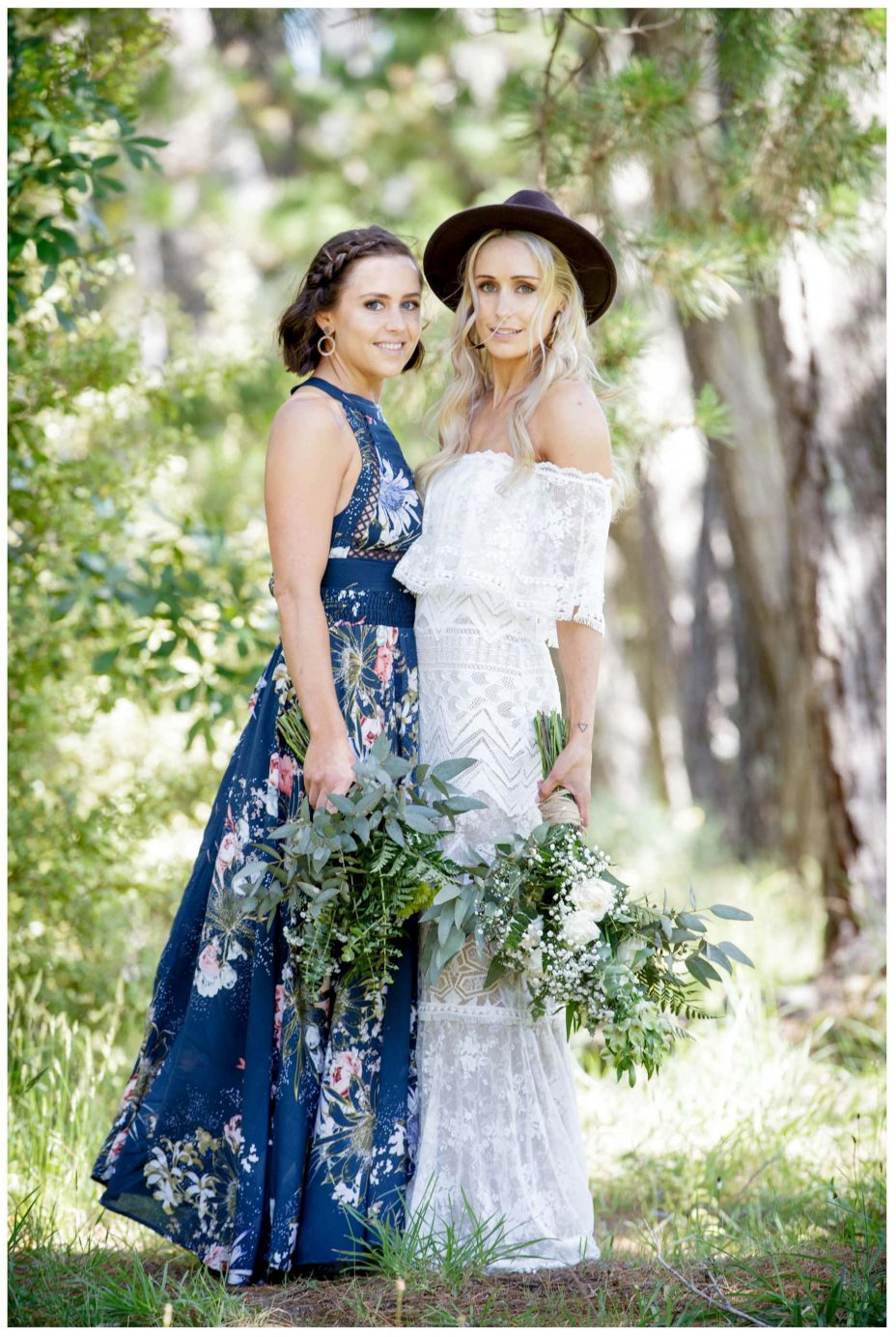 Aussie Bride and maid of honor in blue floral patterned dress look back to camera, Murawai Beech wedding photo