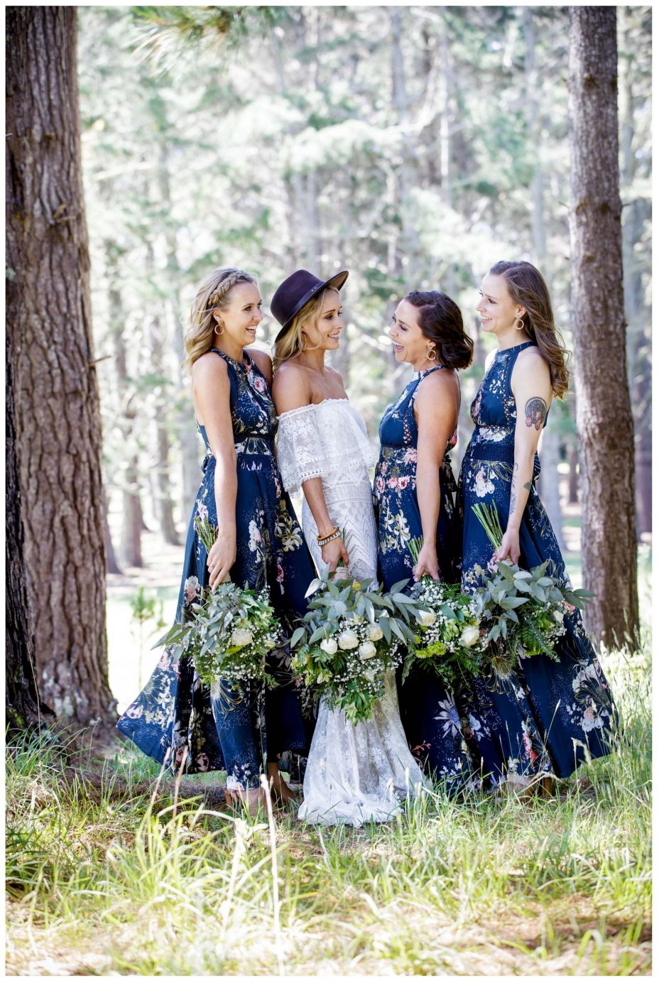 Bride and bridesmaids in blue floral patterned dress look back to camera, Murawai Beech wedding photo