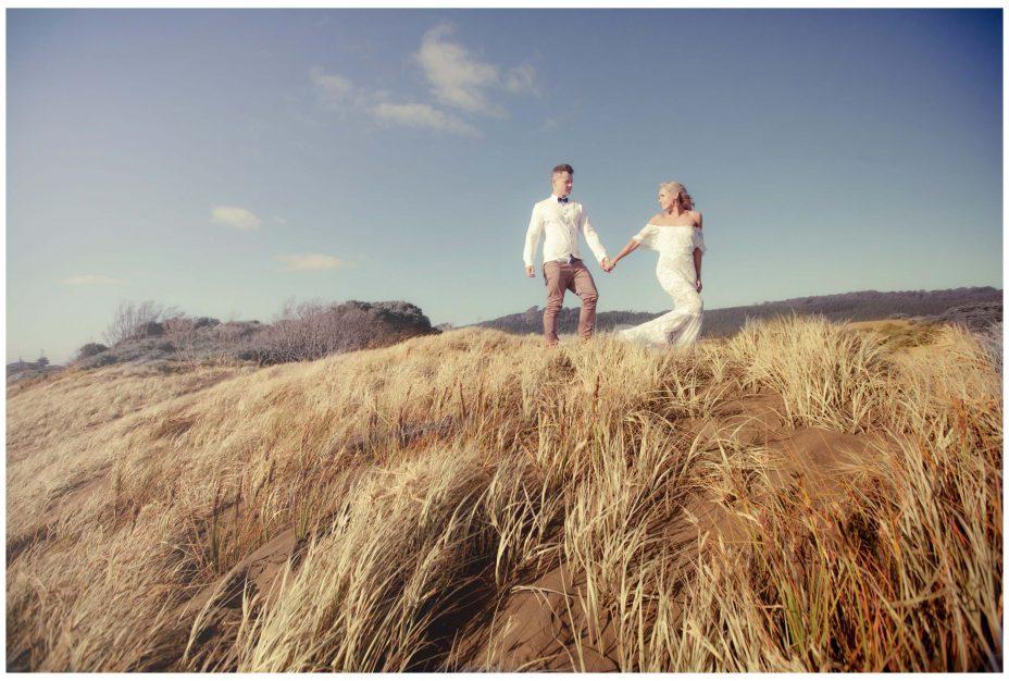 Aussie Bride in lace wedding dress and groom hold hands, Murawai Beech romantic sunset weddimg photo,Auckland New Zealand
