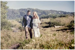 Aussie Bride and groom walk together in sand dunes Murawai Beech, Murawai Beech Wedding photo