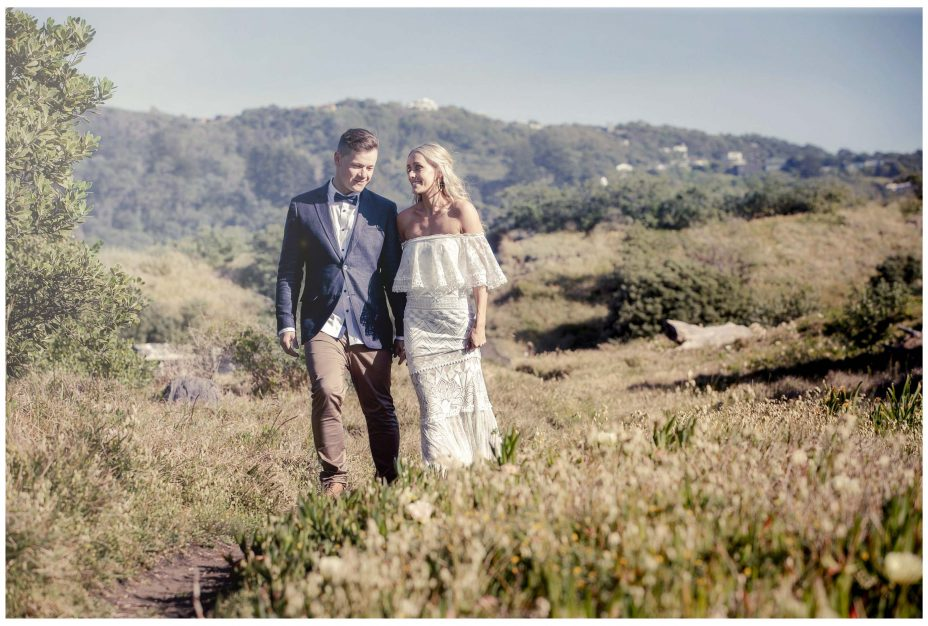 Aussie Bride and groom walk together in sand dunes Murawai Beech, Murawai Beech Wedding photo