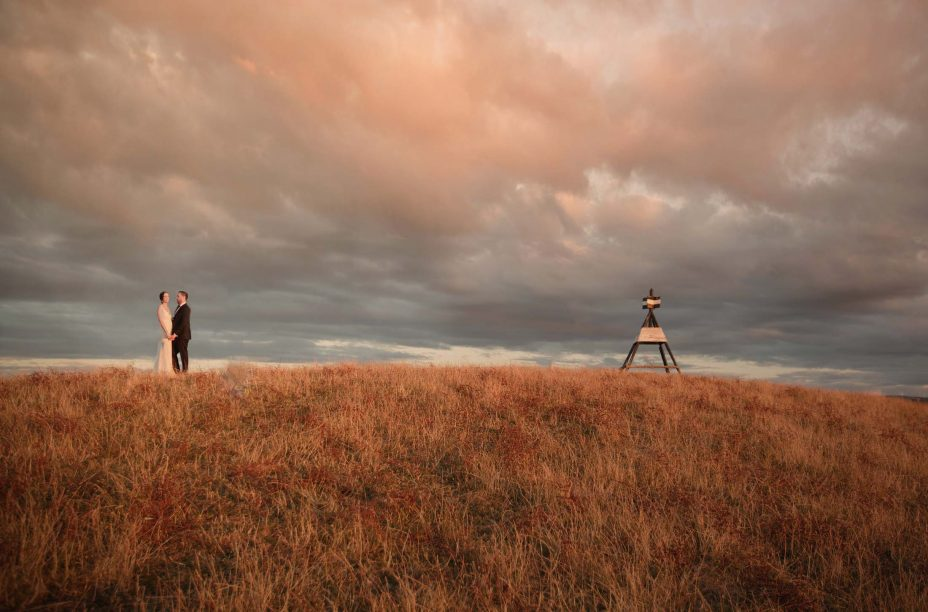 Bride & Groom walk over hill sunset at Kauri Bay Boomrock Auckland