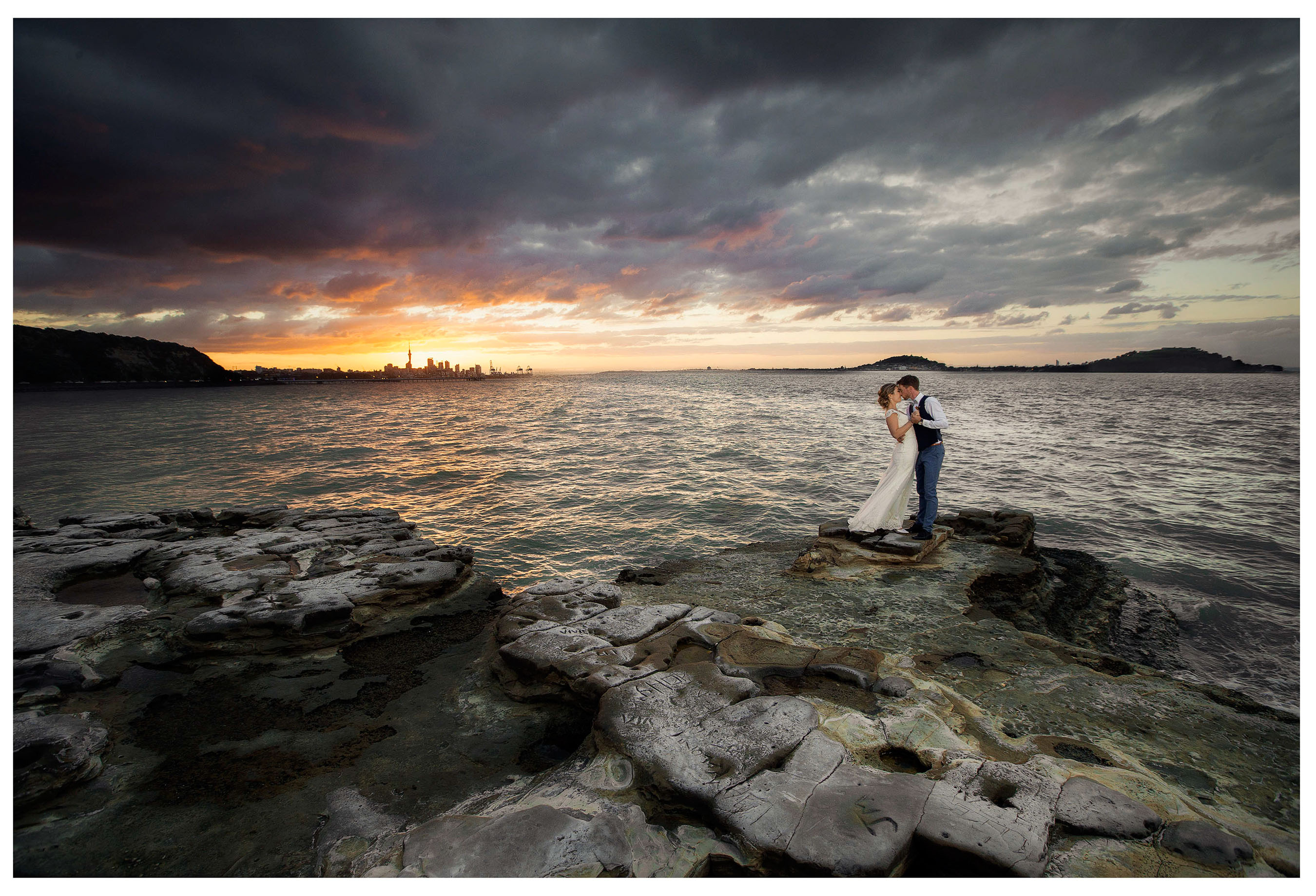 Bride and groom pose on rocks of Five Knotts wedding venue at sunset with view if Auckland City behind them