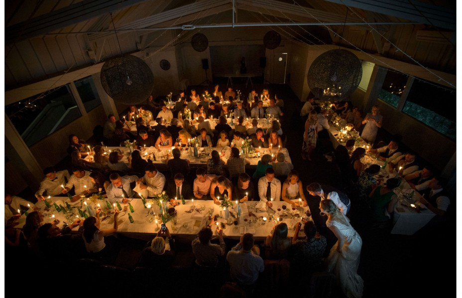 Wedding guests seated on tables in rows lit with golden yellow candlelight as the bride and groom wonder from table to table blowing the candles out at Five Knots wedding venue in Auckland. capturing the moment by Auckland Wedding photographer Chris loufte.