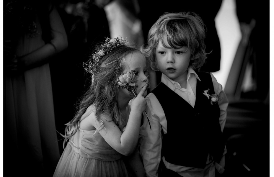 Capturing the moment.Flower girl whispers into page boys ear during wedding ceremony at Five Knots venue in Auckland.