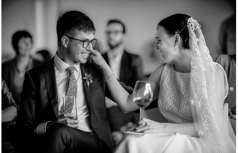 Bride in white lace wedding dress with lace veil smiles as she touches her smiling groom's face at Ponsonby Central Auckland wedding photo by Auckland wedding photographer Chris Loufte