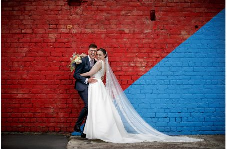 Bride in white lace dress and groom cuddle together and laughing joyfully to camera infront of old red painted brick wall with industrial window by Auckland waterfront.