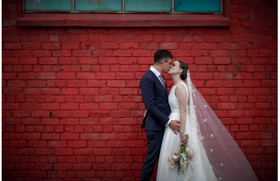 Bride in white lace dress and groom kiss passionatly infornt of old red painted brick wall with industrial window by Auckland waterfront.