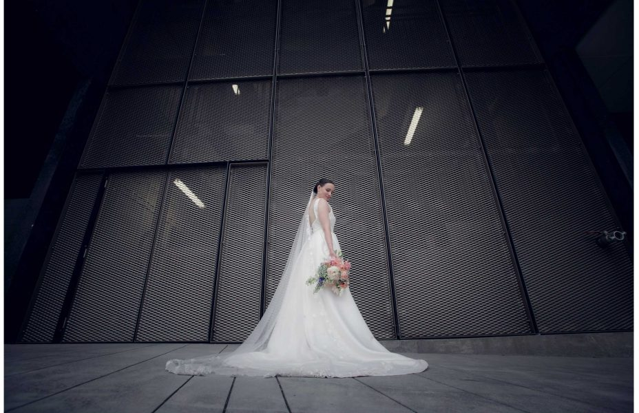 Bride in white lace dress infornt of industrial mesh wall by Auckland waterfront.