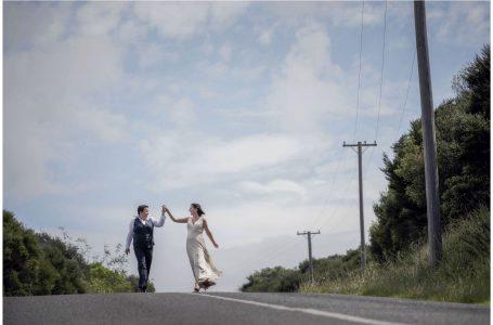 Same sex couple walk down the road together hand in hand in the sunshine on Waiheke Island