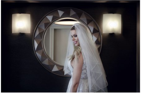 photo of bride wearing a veil infront of a large mirror.