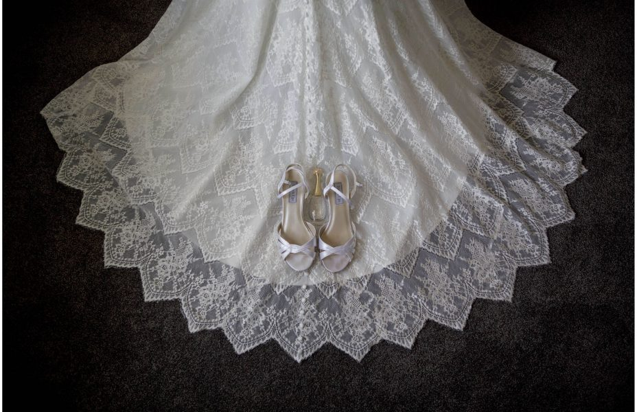 Wedding shoes placed on the train of a wedding dress