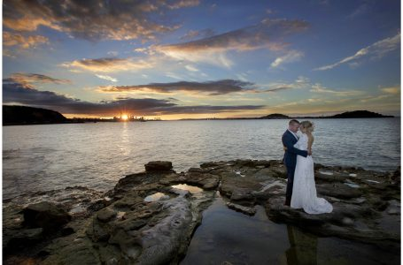 Bride and groom on the rocks as sun sets over Auckland City skyline, Auckland Weding Photographers Five Knotts Wedding