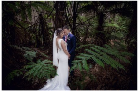 Bride and groom pose for wedding photo in woods near Kumeu Auckland