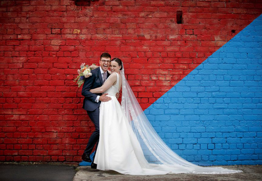wedding-photo-bride-and-groom-happy- joyful by-colourful-wall--Auckland