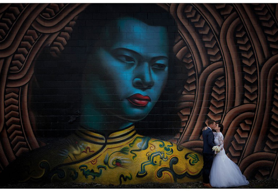 wedding-photo-bride-and-groom-embracing-by-colourful-wall-mural-morningside-Auckland
