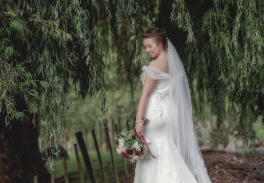 Kumeu weddding bride in white dress under willow tree