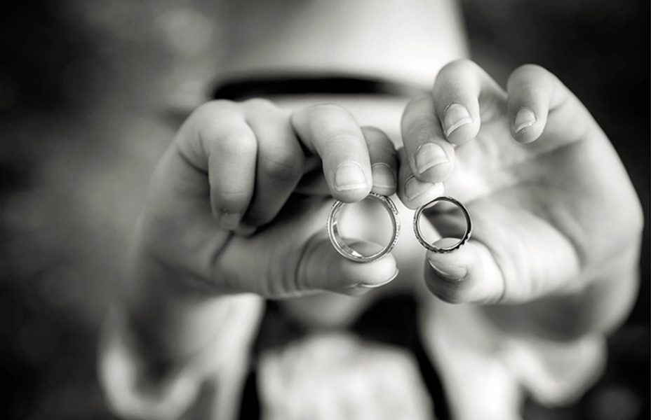 pageboy holds up wedding rings