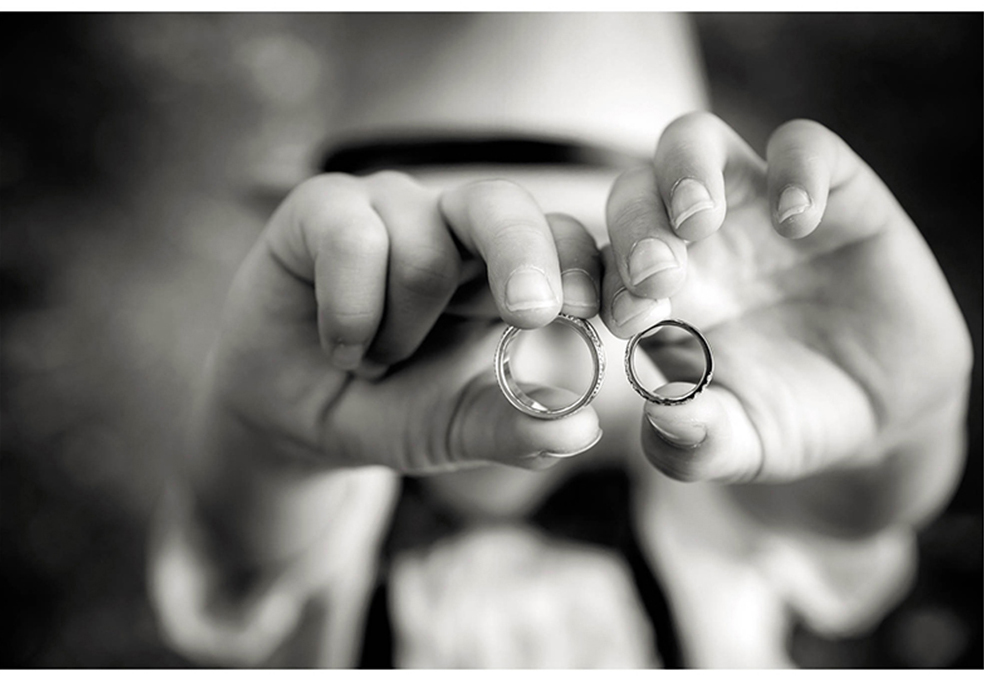 Black-and-white_photo-of-stylish-boy-holding wedding-rings