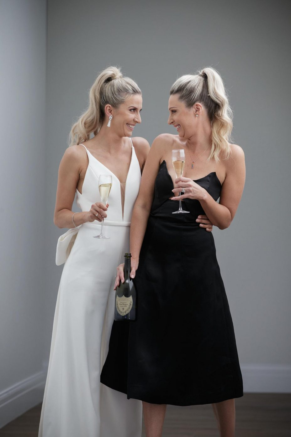 Cute slim bride wearing ivory pant suit and Mi Piaci cream leather boots with her bridesmaid in little black dress pose for fun champagne photo with a bottle of Dom Perignon at the wedding reception in The Northern Club Auckland