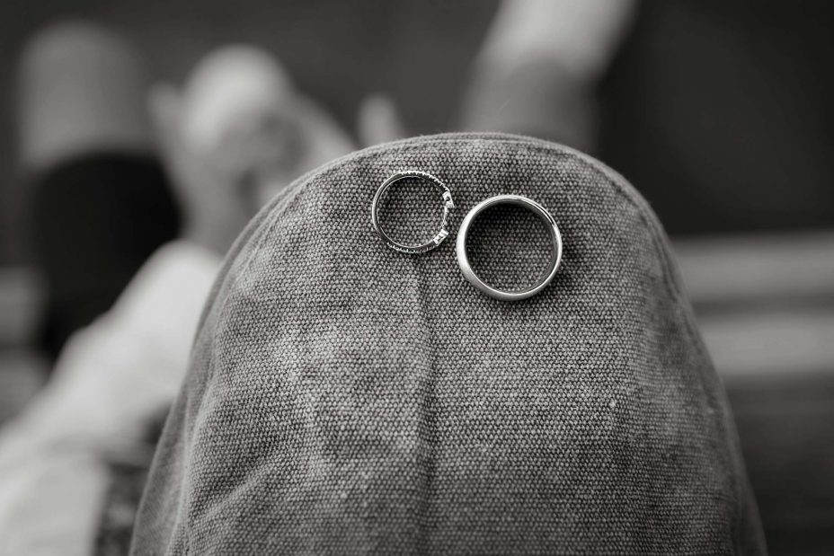 Black and white photo pf wedding rings on a cloth cap hat