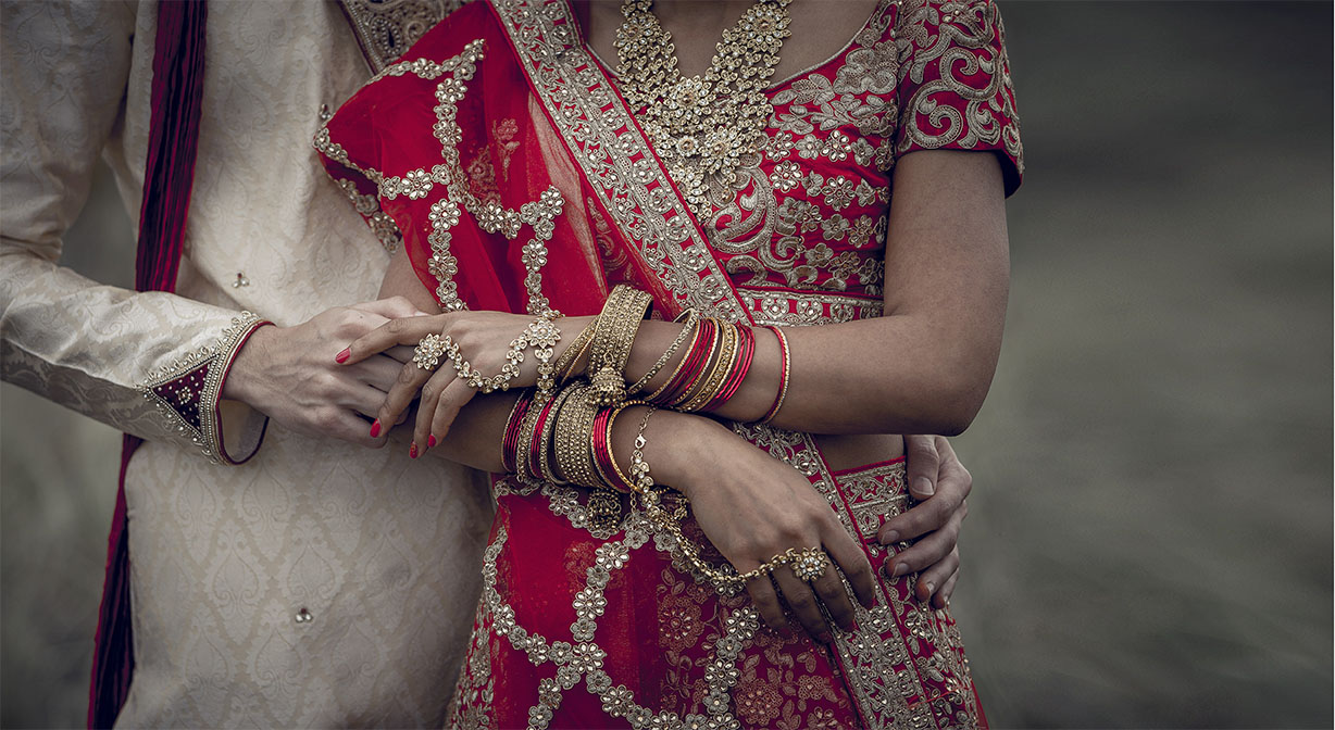 Indian bride wearing traditional red and gold sari with lots of gold jewellery holds hands with her new husband wearing an ivory coloured sherwani posing for their Indian wedding photographer at Muriwai Beach in Auckland..