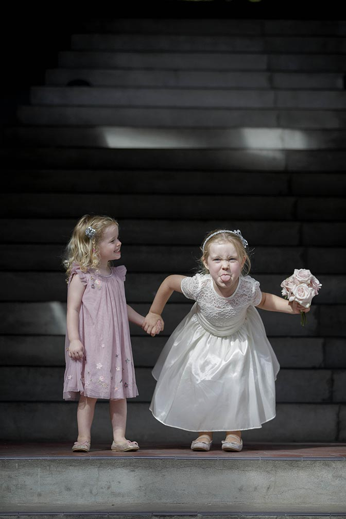 Little flower girl wearing white wedding style dress sticks her tounge out at the photographer whilst holding the hand of smiling flower girl wearing a pink dress. Auckland wedding photo by Chris Loufte at Cibo in the City. Capturing the moment.
