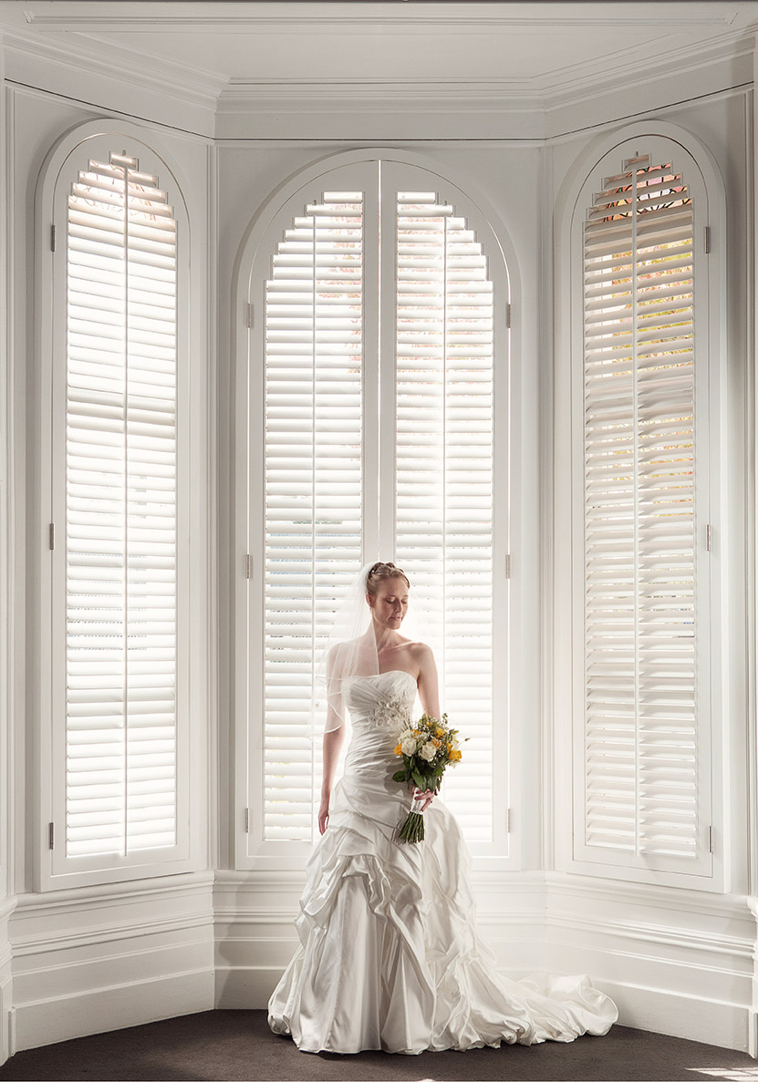 Wedding day bride wearing full length silk wedding gown holding a flower bouquet of yellow flowers standing in front of a double height ornate window with plantation shutters at Diocesan School Auckland.
