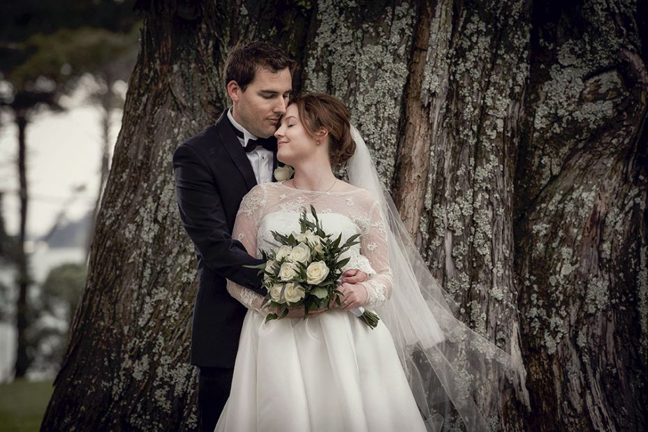 Capturing the moment.Wedding day bride wearing silk ivory coloured wedding dress holding bridal flower bouquet of ivory color roses and groom wearing black tuxedo cuddled together with their eyes closed lent onto the trunk of a huge pine tree in Auckland's Cornwall Park. Capturing the moment by Auckland Wedding photographer Chris loufte.