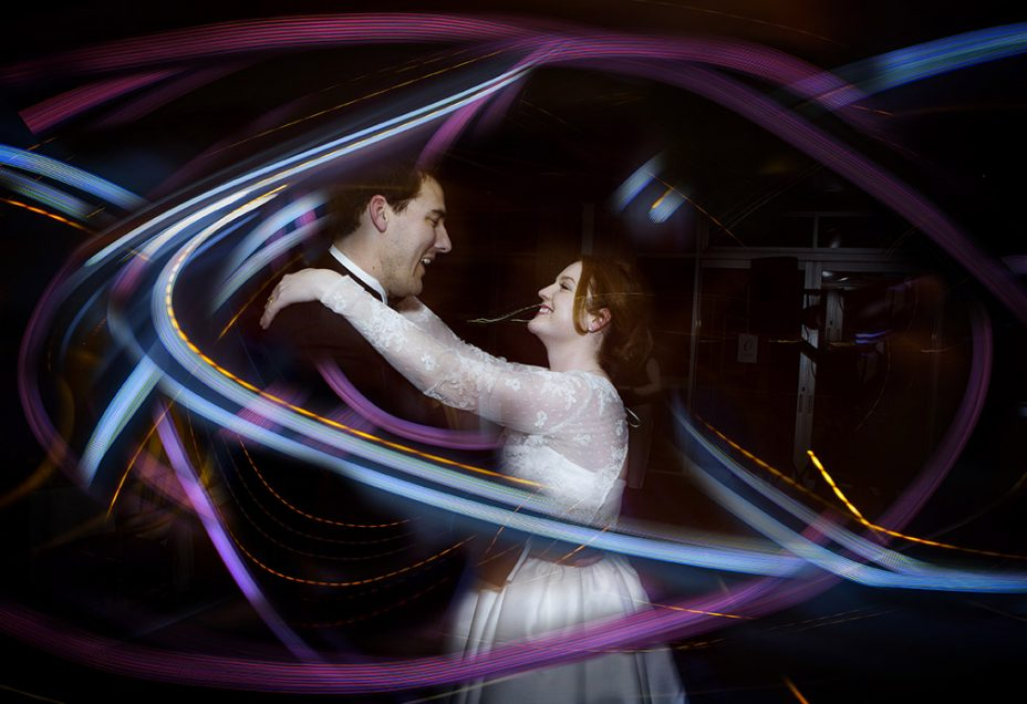 Capturing the moment.Wedding day bride wearing silk ivory coloured wedding dress and her new husband look into each other's eyes smiling during their first dance whilst surrounded by streaks of blue and purple light. .capturing the moment by Auckland Wedding photographer Chris loufte.