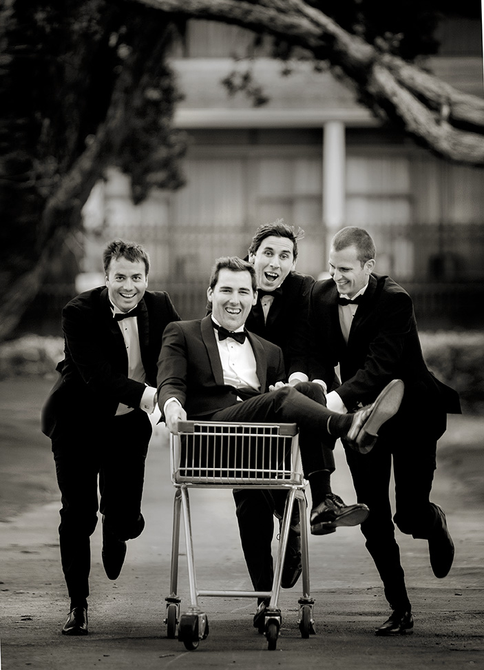 Three groomsmen dressed in matching black tuxedos pushing the groom in a shopping trolly along a road in Auckland as they get him to the church on time for his wedding at the Roman Catholic Cathedral of St PAtrick & St .joseph in Auckland. capturing the moment by Auckland Wedding photographer Chris loufte.