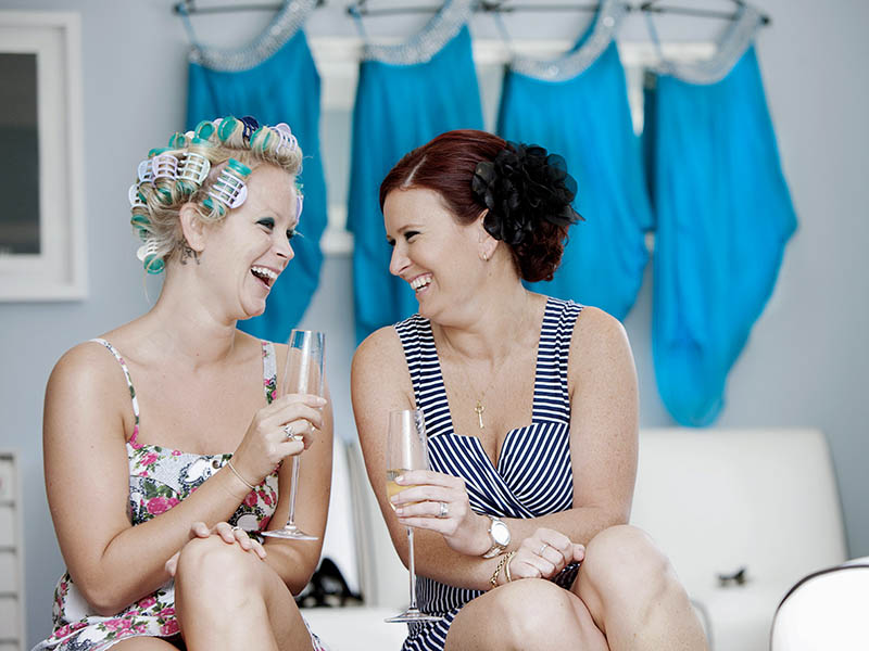Two bridesmaids sit on a couch drinking champagne looking at each other and laughing. One has her hair in curlers. Behind the, are four light blue dresses hung up on the wall in the bridal preparatio room at Kelliher Estate Auckallnd.