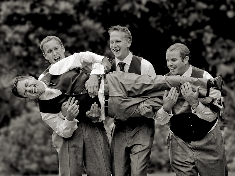 Wedding-day-groomsmen- laugh as they pick up and hold the laughing groom horizontally. Cahir Loufte wedding photographer capturing the moment for a fun wedding photo.