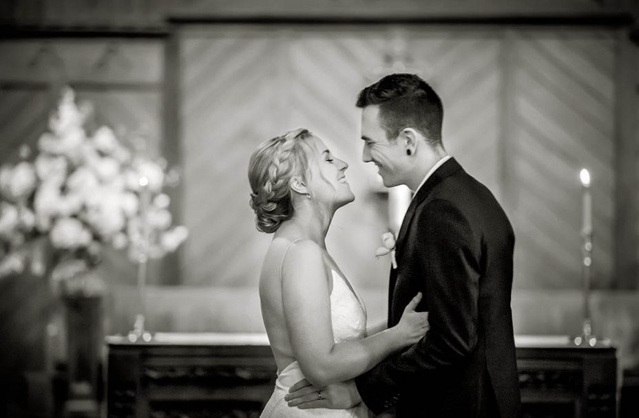 Bride wearing strapless white wedding dress and her new husband wearing a black suit look into each others eyes and smile in front of the alter at Saint Aidan's Church in Remuera in Auckland during their wedding ceremony. Capturing the moment by Auckland Wedding photographer Chris Loufte