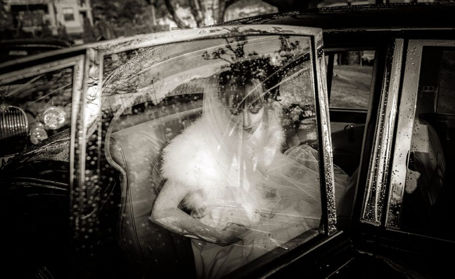Bride wearing white wedding day is framed by the chrome window frame of a classic black wedding limousine. Raindrops on the window.