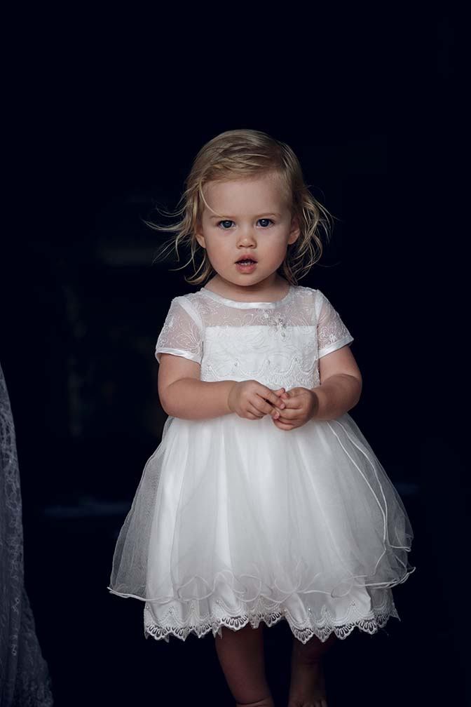 Cute flower girl wearing white sating dress has a startled expression as Auckland wedding photographer Chris Loufte captured the moment.