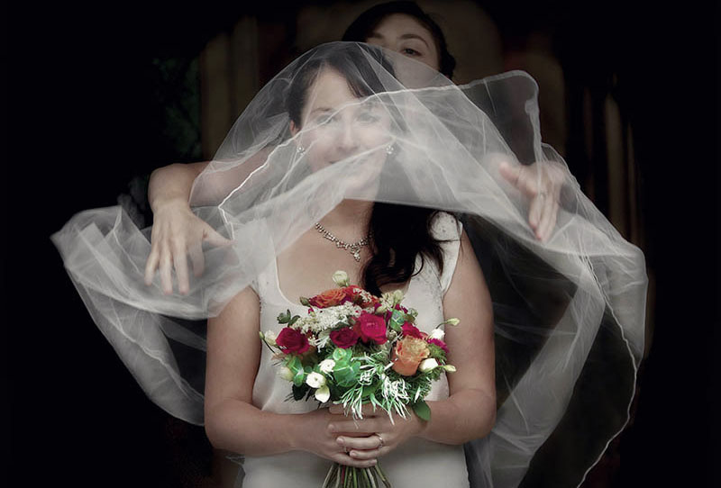 wedding day bride holding a brightly coloured flower bouquet has her veil thrown over her head in preparation for her ceremony.
