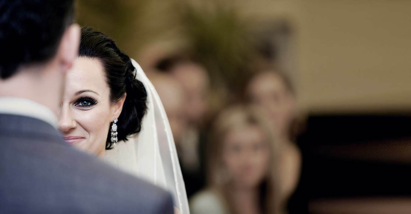 Close up photo of bride smiling at the groom during their wedding ceremony photographeed by Chris Loufte Auckland wedding photographers
