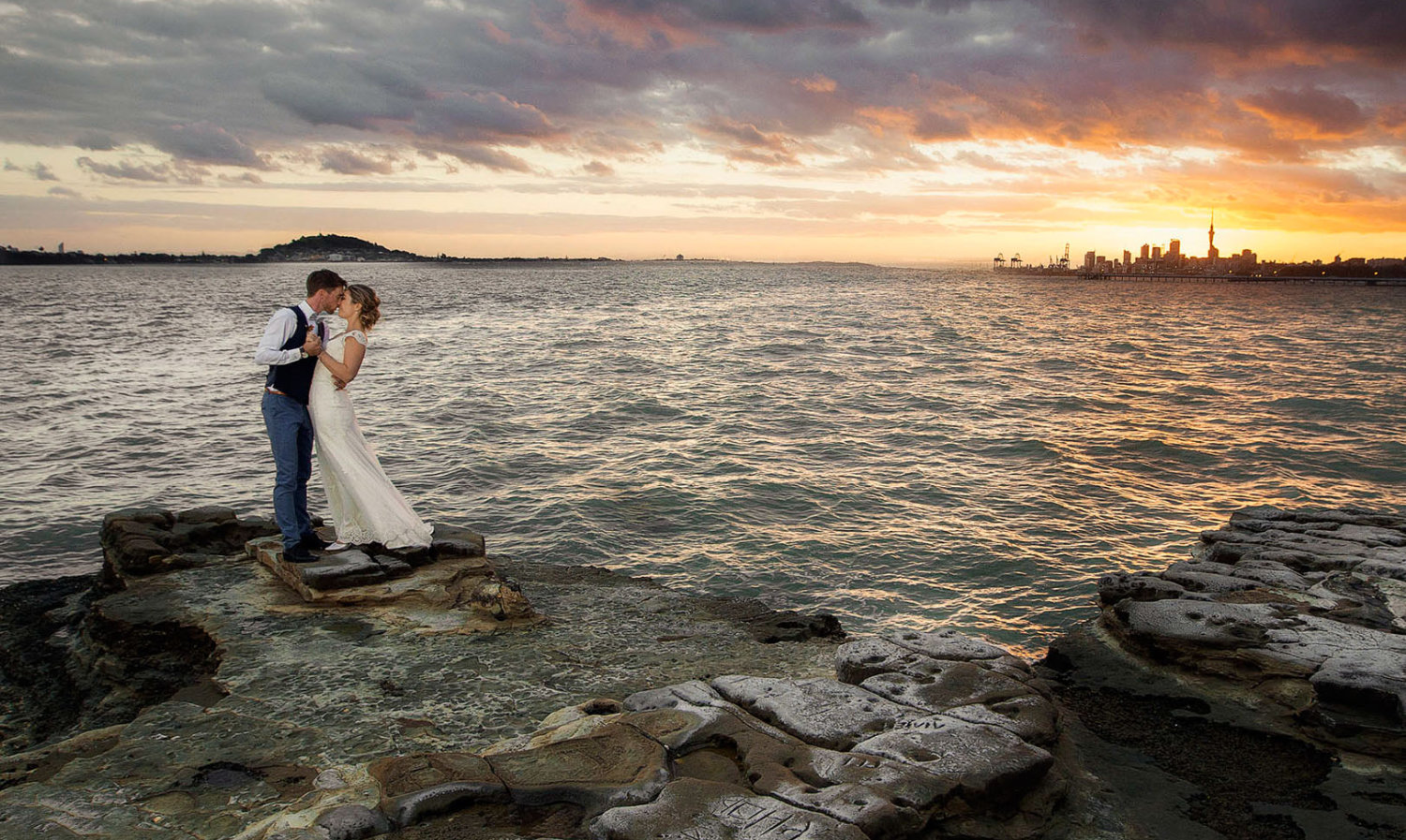 Bride and groom kissing on rocks by the sea with auckland city behind. Auckland wedding photographers sunset photo