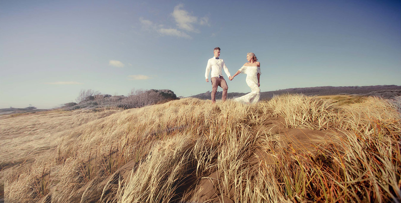 Young bride wearing white lace wedding dress leads her new husband through the long grass on the sand dunes of Muriwai Beech in Auckland in the golden afternoon sun.