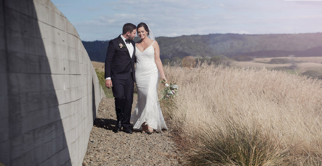 Bride wearing figure hugging white wedding dress and groom wearing classical black tuxedo an bow tie smile and walk close together along gravel path in the afternoon sun on their way to their wedding reception at Kauri Bay Boomrock