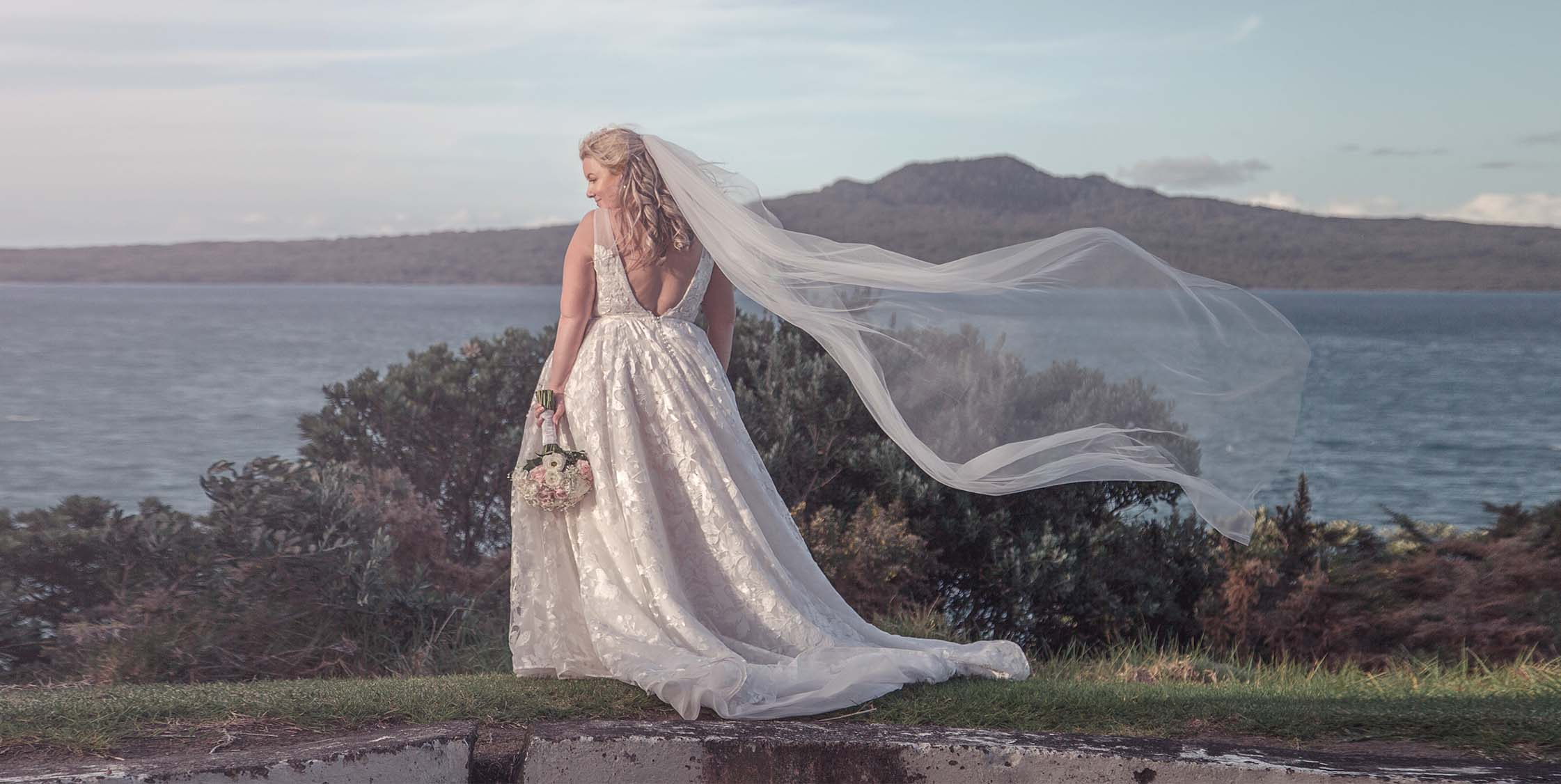 Sunset wedding photo of bride in white wedding dress with her Veil blowing in the wind holding her bridal flower bouquet posing for Chris Loufte Auckland Wedding Photographers in front of Rangitoto island at Fort Takapuna and the Officers Mess on a sunny evening in Auckland.