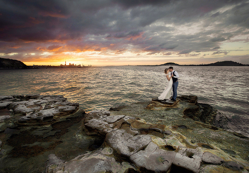 wedding-photo-bride-and-groom-embracing-at-sunset-on-rocks-Tamaki_yacht_club