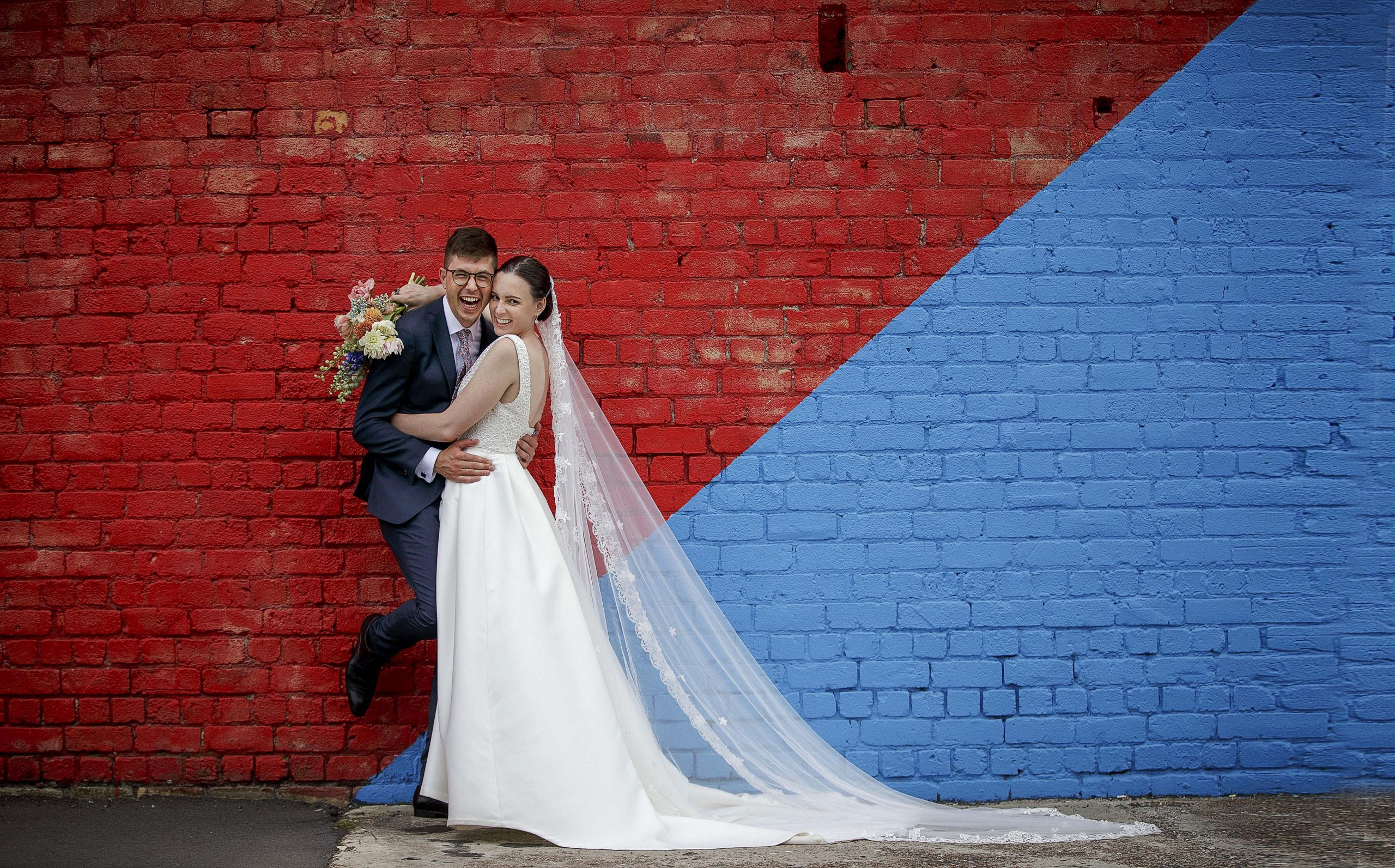 bride and groom laugh together for a wedding photo  in front of blue and red brick wall in Auckland city centre